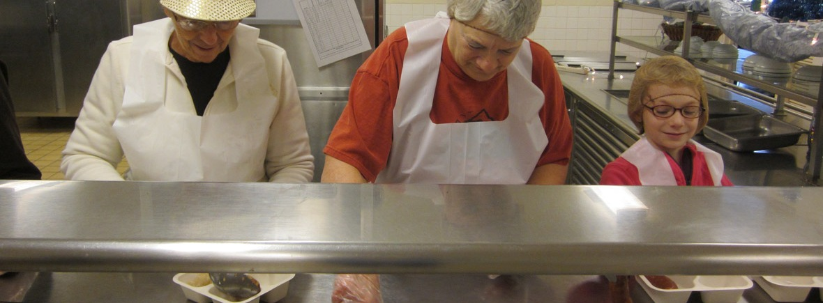 two women and a girl serve food in a cafeteria line